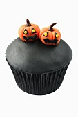 A black muffin decorated with marzipan pumpkins