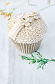 A celebratory cupcake decorated with sugar pearls and sugar flowers
