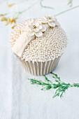 Festlich dekorierter Cupcake mit Zuckerperlen & Zuckerblumen