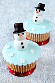 Two wintry cupcakes decorated with snowmen