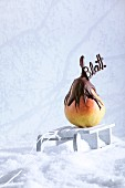 A pear dipped in chocolate, with chocolate writing, at Christmas