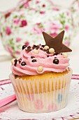 A pink cupcake decorated with a chocolate star in front of a teapot