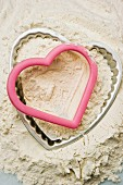 A heart-shaped baking tin and cutter in a mound of flour