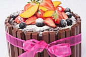 Chocolate torte with fresh fruit, icing sugar and a pink ribbon