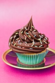 A chocolate cupcake with sugar strands on a pink plate