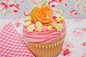 A pink cupcake decorated with a sugar rose and sweets