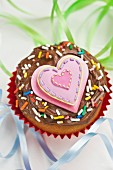 Cupcake with chocolate icing, sugar strands and a pink heart between streamers