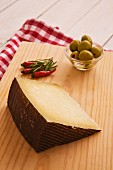 A wedge of Manchego, chillies and a small bowl of olives on a wooden board