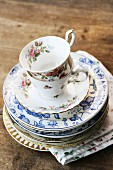 Stacked, vintage china teacups, saucers and plates