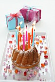 A birthday cake with lit candles being blown out, and wrapped presents