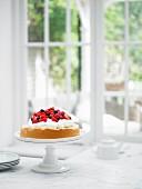 Biskuitkuchen mit Sahne und Beeren auf Kuchenständer vor Fenster