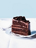 A slices of chocolate mousse layer cake with chocolate curls