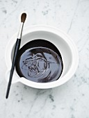 Melted chocolate in a bowl with a paintbrush