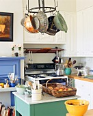 Landhausküche mit Mittelblock unter abgehängtem Kochgeschirr an der Decke