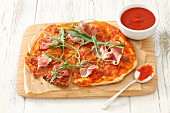 Pizza with dry-cured ham and rocket