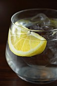A glass of water with a wedge of lemon and ice cubes