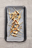Satay skewers on a baking tray