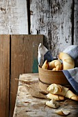 Croissants in a wooden basket on a rustic wooden table