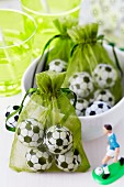 Chocolate footballs packed in green organza bags