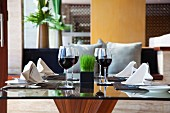A table laid for a meal with four place settings and glasses of red wine