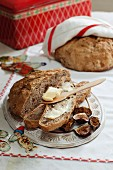 Spelt bread with walnuts and dried figs with a slice spread with butter