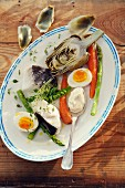 Provencal appetiser featuring artichokes, poached cod, vegetables, eggs and aioli
