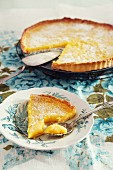 French lemon tart, sliced with a piece on a plate