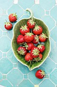 Fresh strawberries in a green, leaf-shaped bowl (view from above)