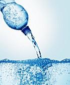 Wasser aus Flasche in ein Wasserbecken gießen