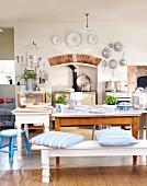 weiße Bank mit Sitzkissen und rustikale Tische vor Küchenherd in Nische in ländlicher Küche