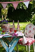 Antiker Stuhl mit ländlichen Stoffbezug neben Tisch mit Erfrischungsgetränken unter Wimpelgirlande im Garten