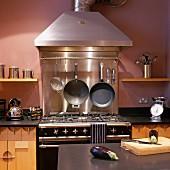 Gasherd im Vintagelook mit Edelstahl Dunstabzug an violett getönter Wand in moderner Küche