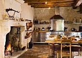 Rustikale Landhausküche mit Edelstahl-Küchenzeile, Esstisch aus Holz & offenem Kamin