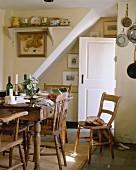 Gedeckter, rustikaler Esstisch aus Holz mit Holzstühlen in Landhausküche