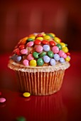 A muffin decorated with Smarties