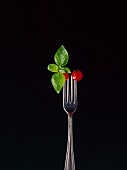 Basil and two cocktail tomatoes skewered on a fork