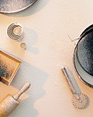 Baking tins and utensils on a floured work surface