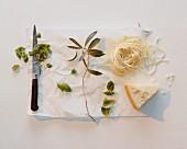Frische Tagliatelle, Parmesan & Basilikumblätter mit Messer auf Papier