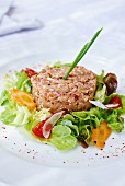 Veal tartare in a ring of salad