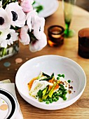 Pea salad with asparagus, courgette flowers, and a carrot & yoghurt sauce