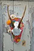 Geweisseltes und mit chinesischem Geschenkpapier beklebtes Geweih, Strohblumen-Girlande und Briefmarke auf alter Holztür mit abblätternder Farbe