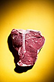Raw T-Bone Steak on a Yellow Background