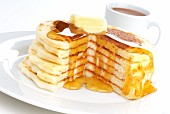 A Stack of Large Pancakes with Butter and Maple Syrup and a Cup of Coffee