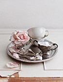 Antique teacups, a sugar bowl and a pink rose flower