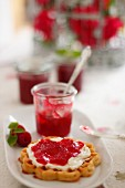 A waffle topped with raspberry and rose jam