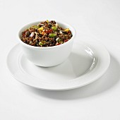 Red Quinoa Salad with Mango, Onion and Soy Beans in a White Bowl on a White Plate