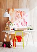 Weisser Arbeitstisch mit gelbem Stuhl; darüber ein abstraktes Aquarellbild