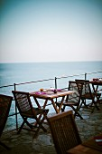 A table laid for a meal on a terrace at the seaside