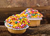 Cupcakes decorated with colourful chocolate beans