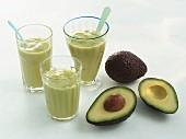 Avocado und drei Gläser Avocado Smoothie